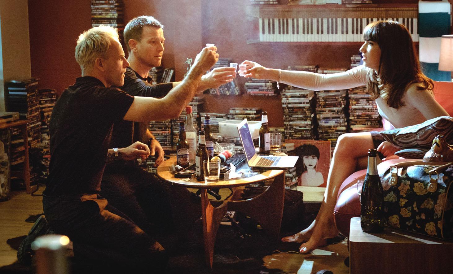 Simon (Jonny Lee Miller), Renton (Ewan McGregor) and Veronika (Anjela Nedyalkova) drinking in SimonOs flat in TriStar PicturesO T2 TRAINSPOTTING